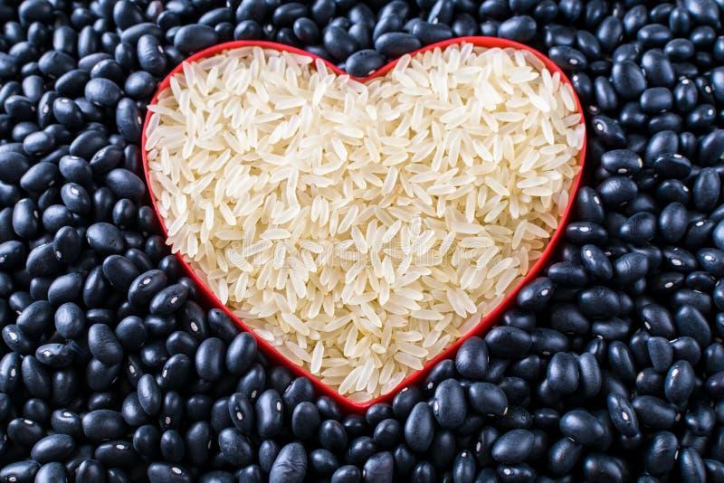Ruwe voedselrijst en zwarte bonenachtergronden stock foto's