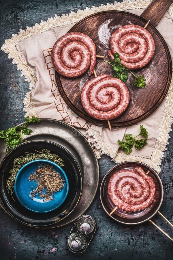 Ruwe worst op uitstekende scherpe raad met kruiden en kruiden, voorbereiding op donkere rustieke keukenlijst stock foto
