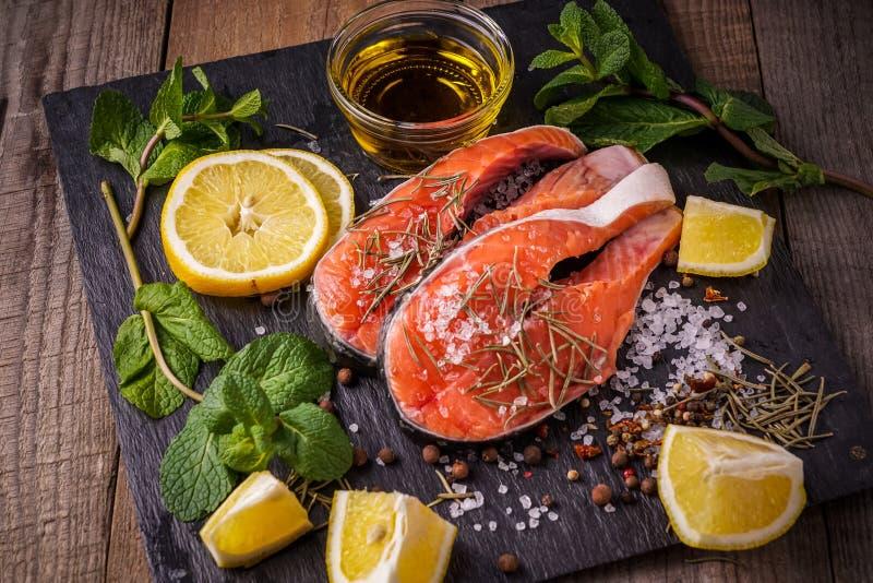 Ruwe zalmvissen alvorens, met olijfolie, rozemarijn, munt voor te bereiden royalty-vrije stock afbeeldingen
