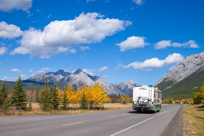 An RV aon the highway through the Canadian Rocky Mountains in Kananaskis, Alberta during the peak of autumn colors royalty free stock images