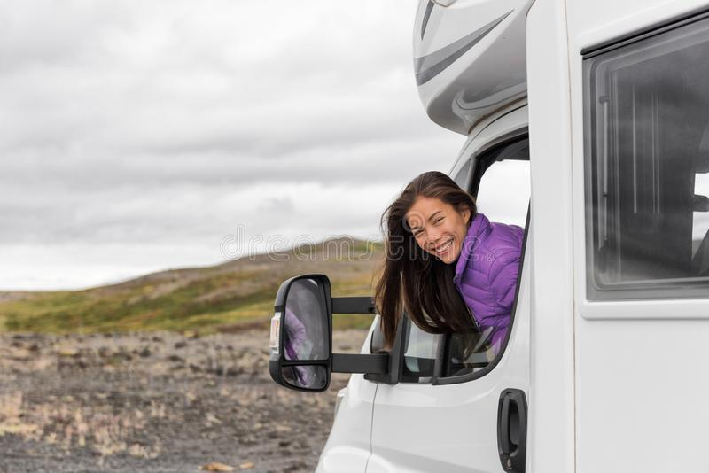 RV camper trailer travel woman driving motorhome camping van on Iceland road trip. Asian tourist driver smiling peeking out window stock image