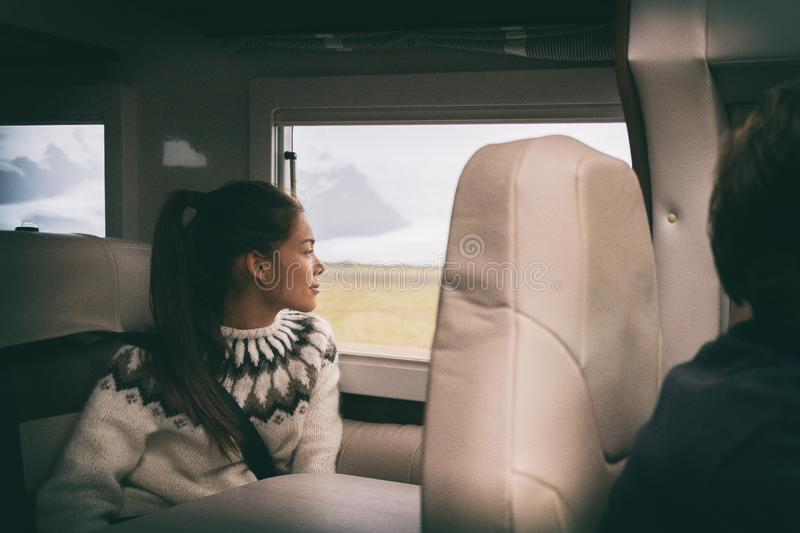 RV camper van travel Asian girl sitting in back of motorhome car on Iceland road trip. Vacation lifestyle royalty free stock image