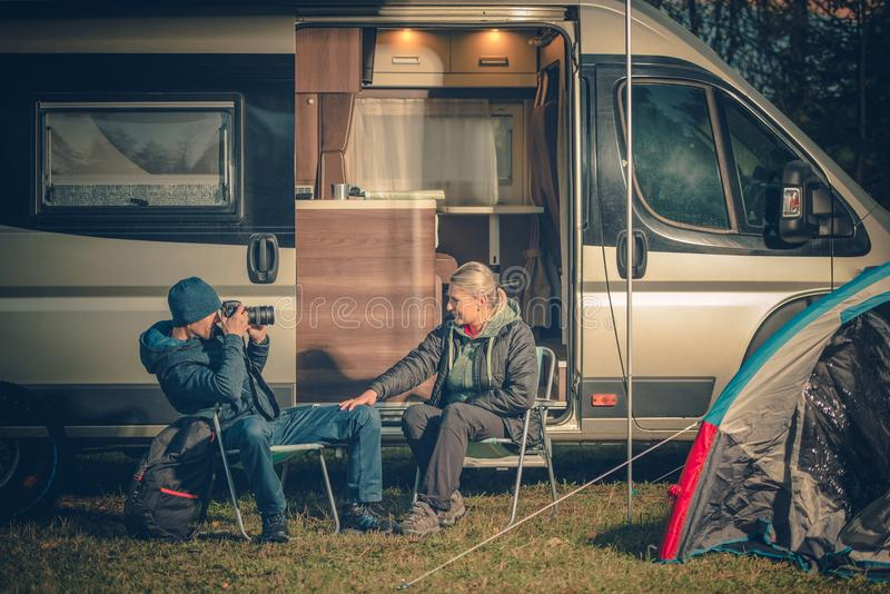 RV Camping Couples Fun. Young Couples Having Fun on the Campsite. RV Motorhome Camping. Men Taking Picture of His Wife Using Digital Camera royalty free stock images