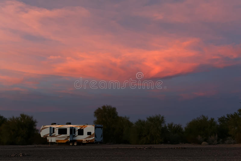 Rv grande solamente contra las nubes de la puesta del sol imagenes de archivo