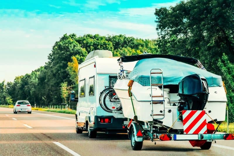 Rv-Kampeerautoauto met motorboot op Weg stock fotografie