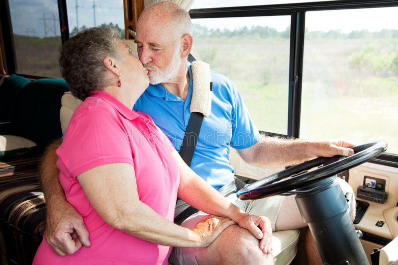 RV Seniors - Driving Distractions. Vacationing senior couple kissing while he is driving their motor home stock images