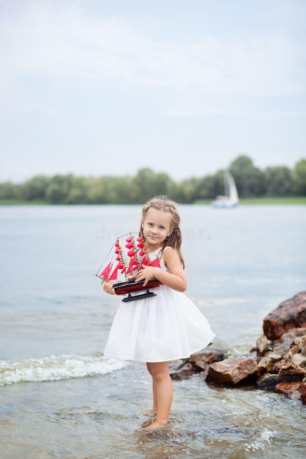 ?rvore no campo Jogo despreocupado da infância feliz na areia aberta O conceito da menina bonito pequena do resto e do escarlate  fotos de stock royalty free