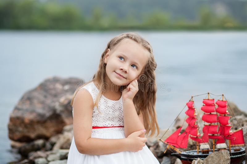 ?rvore no campo Jogo despreocupado da infância feliz na areia aberta O conceito da menina bonito pequena do resto e do escarlate  foto de stock