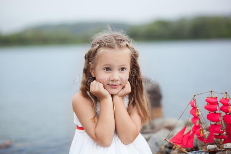 ?rvore no campo Jogo despreocupado da infância feliz na areia aberta O conceito da menina bonito pequena do resto e do escarlate  imagem de stock