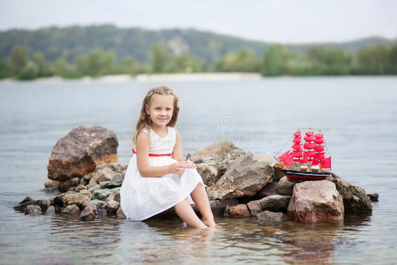 ?rvore no campo Jogo despreocupado da infância feliz na areia aberta O conceito da menina bonito pequena do resto e do escarlate  imagens de stock royalty free