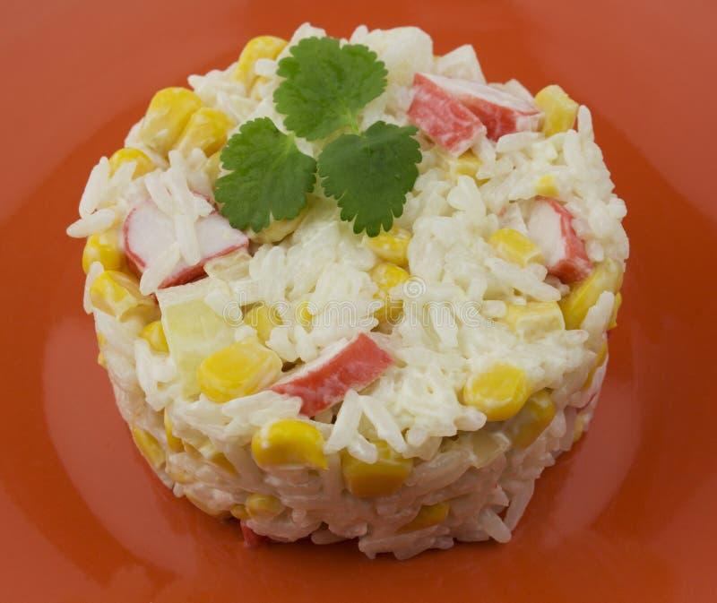 Ryżowa sałatka z krabami kukurydzanymi z majonezowym opatrunkiem słuzyć na pomarańcze talerzu i dekorującym z zieleniami, Eleganc obrazy stock