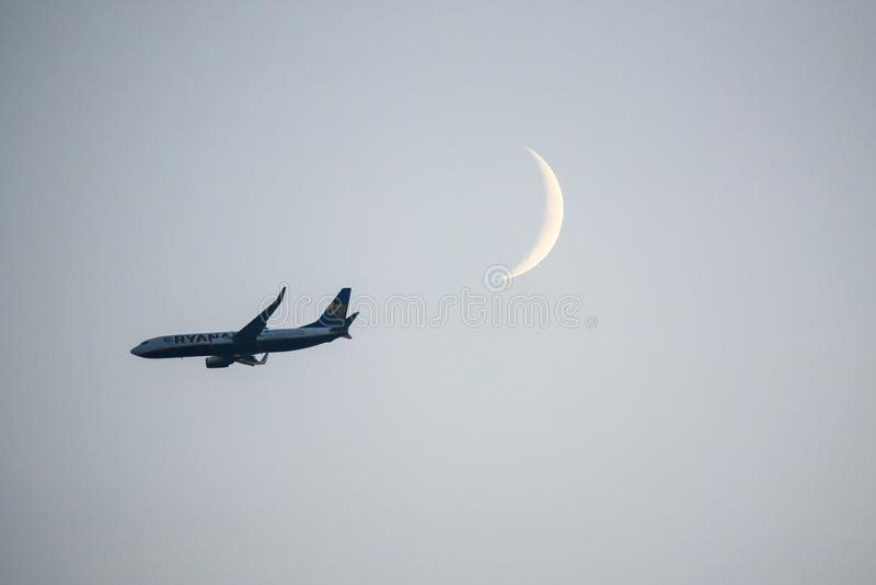 Ryanair airplane flying in the sky in front of moon. RIGA, LATVIA. 6th June 2019. Ryanair airplane flying in the sky in front of moon after sunset before landing stock image