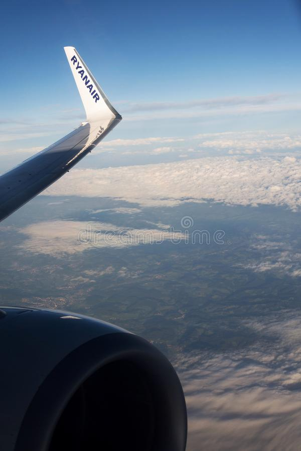 Ryanair Irish low-cost airline Boeing 737 wing during flight with cloudy sky background. MEMMINGEN, GERMANY - JULY 6 2019: Ryanair Irish low-cost airline Boeing royalty free stock photography