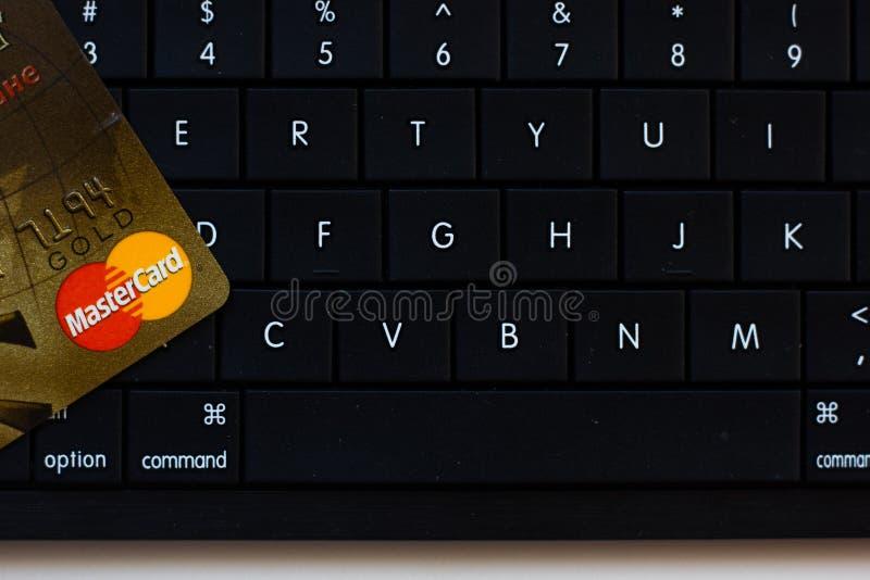 Ryazan, Rusia - 27 de febrero de 2018: Oro de Mastercard de la tarjeta de crédito sobre el teclado negro de la PC fotografía de archivo libre de regalías