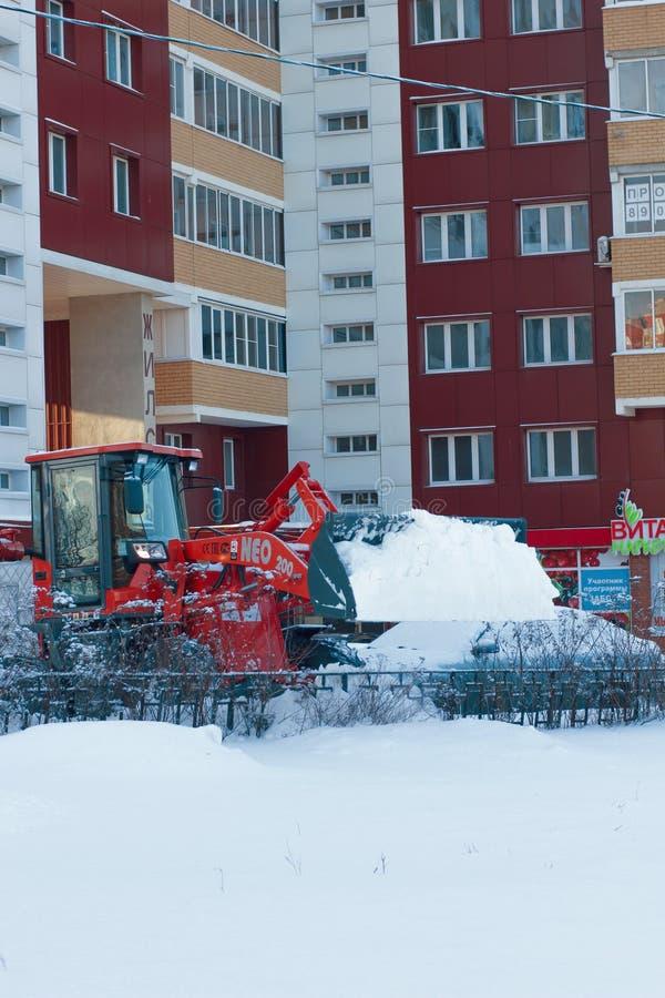 RYAZAN, RUSIA - DICIEMBRE, 15 - calle de la limpieza de la niveladora de la nieve en invierno nevoso fotografía de archivo