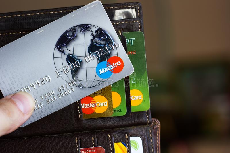 Ryazan, Russia - February 27, 2018: Credit card of Maestro brand over the leather wallet and number of cards. royalty free stock images