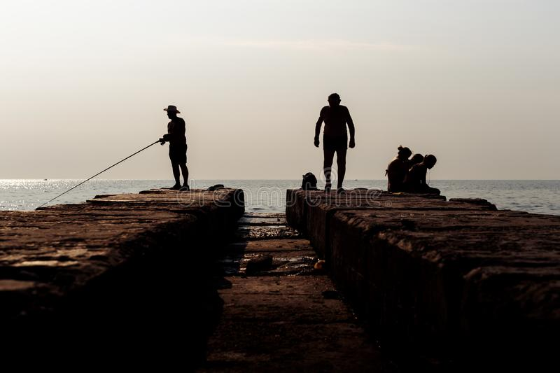 Rybacy łowi na molu Istoty ludzkiej interakcja na falochronie Sylwetki fotografia obrazy stock