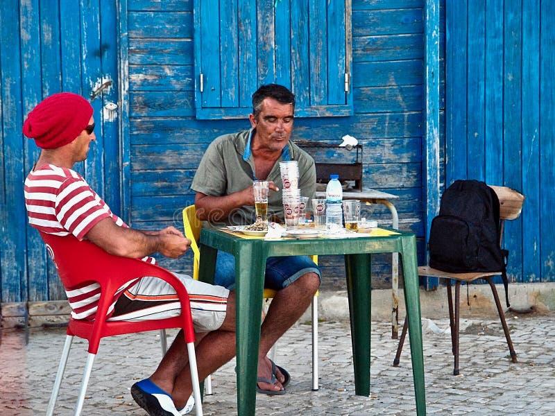 Rybacy je przed Błękitnymi drewnianymi fisher domami w Olhos De Agua w Portugalia fotografia royalty free