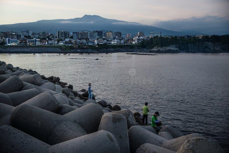 Rybacy na falowych łamaczach po zmierzchu z miastem i wulkanem w tle, Seogwipo, Jeju wyspa, Południowy Korea zdjęcia stock