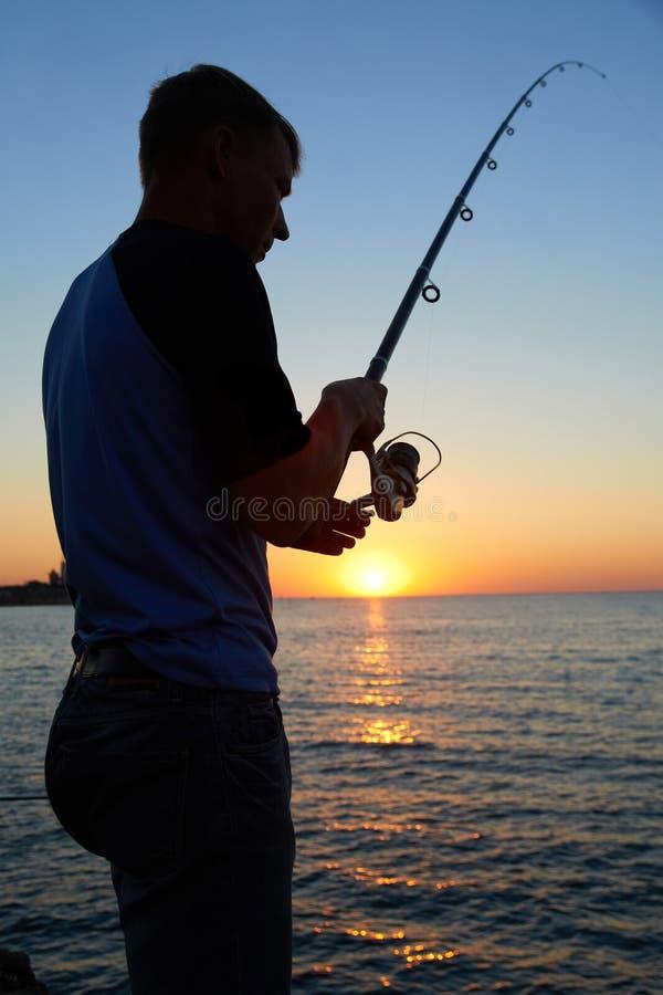 Rybak łowi przy zmierzchem zdjęcie stock