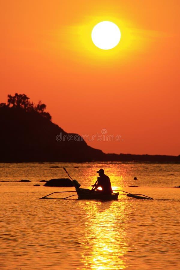 Rybak na łodzi nad dramatycznym zmierzchem fotografia royalty free