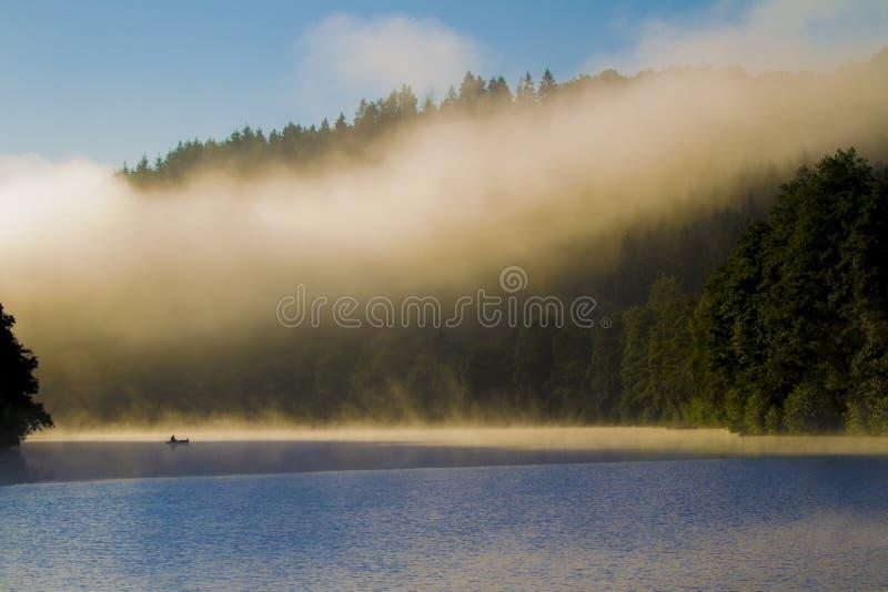 Rybak na drewnianej łodzi przy wschodem słońca w mgłowym dniu zdjęcia stock