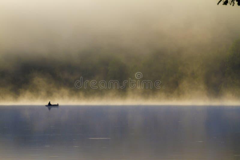 Rybak na drewnianej łodzi w jeziorze przy wschodem słońca w mgłowym dniu fotografia stock