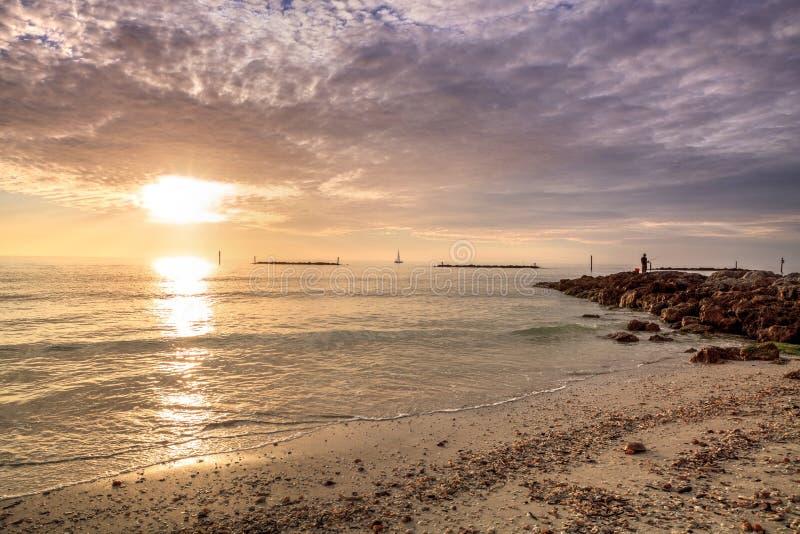 Rybak na skałach Południowa Marco wyspy plaża przy zmierzchem z łodzią w odległości obraz stock