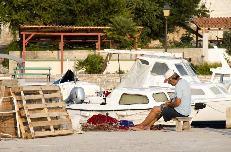 Rybak naprawia jego sieć rybacką na molu zdjęcia royalty free