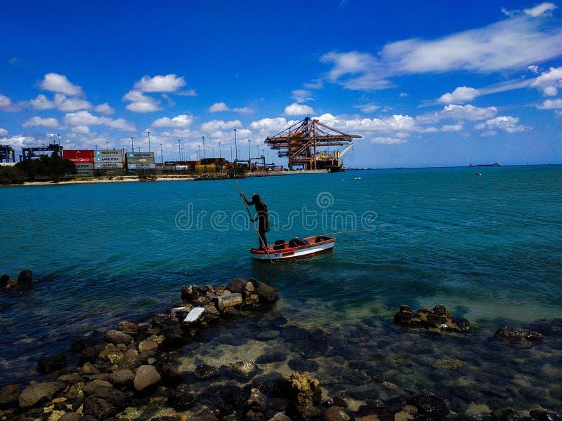 Rybak pracujący na codziennej łodzi rybackiej wpada do morza zdjęcia royalty free