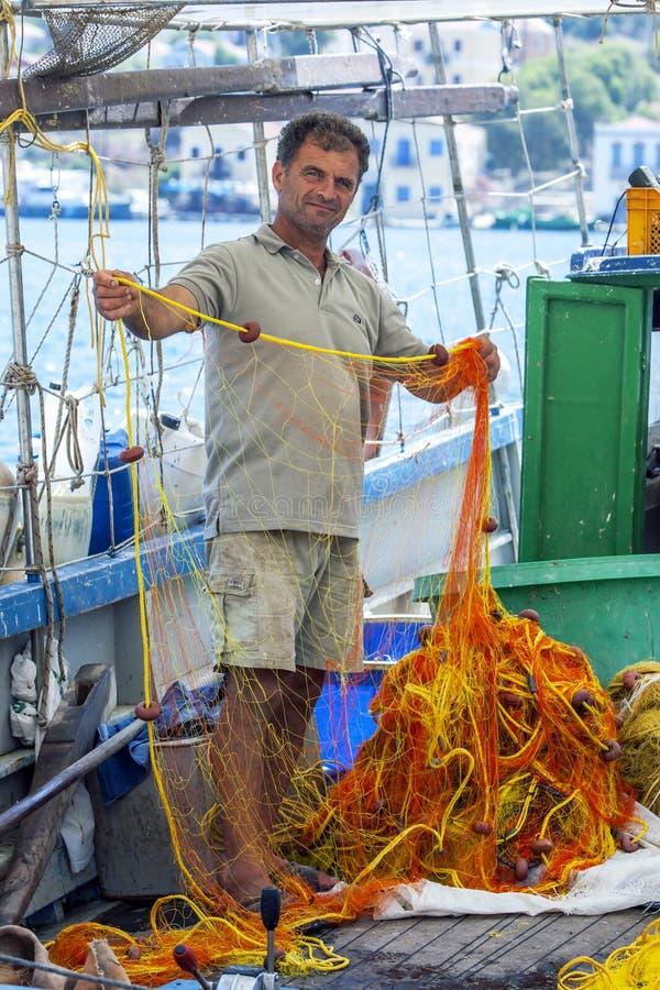 Rybak sprawdza jego sieci dla dziur w schronieniu Grecka wyspa Kastellorizo zdjęcie royalty free