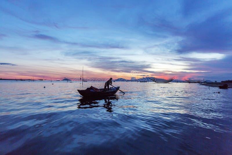 Rybak sprawdza jego sieci w wczesnym poranku na rzece w Hoian, Wietnam zdjęcia stock