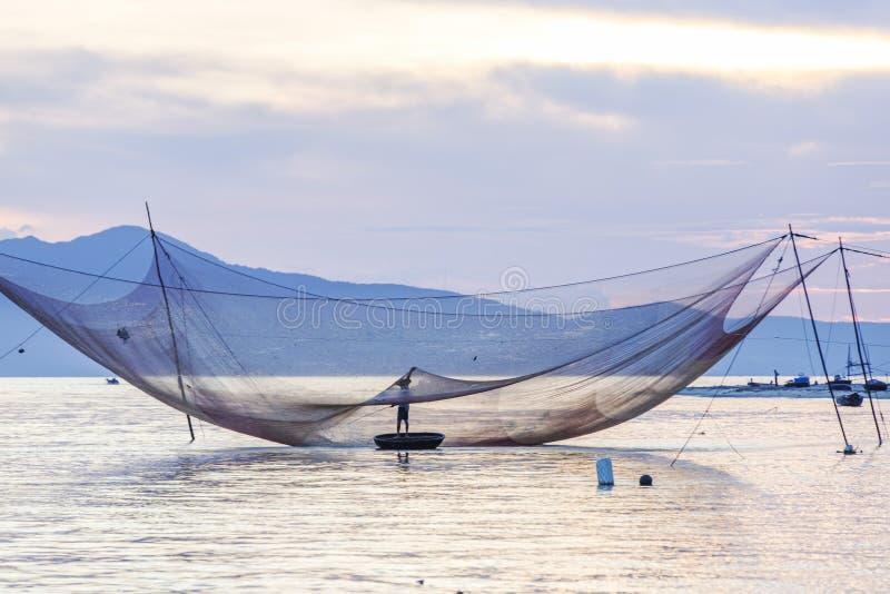 Rybak sprawdza jego sieci w wczesnym poranku na rzece w Hoian, Wietnam obraz stock