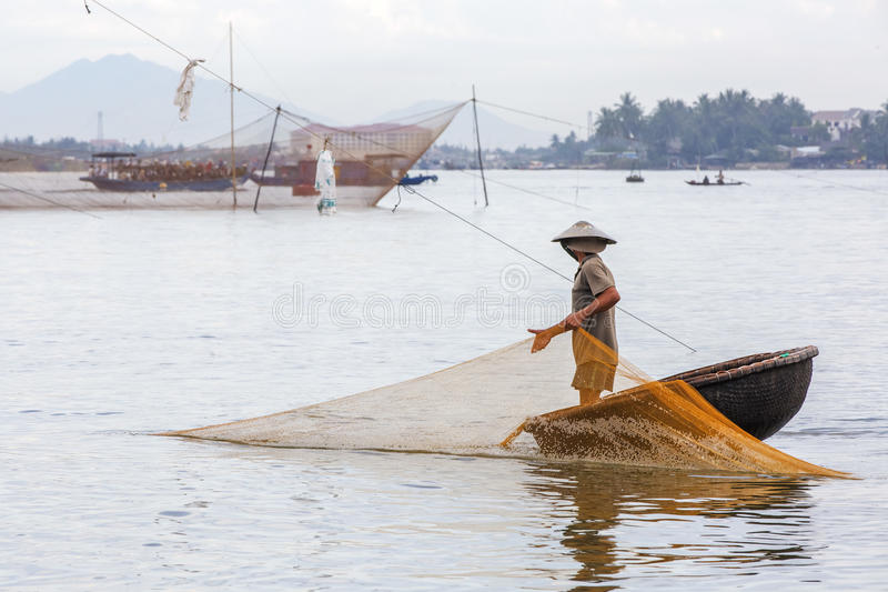 Rybak sprawdza jego sieci w wczesnym poranku na rzece w Hoian, Wietnam obraz royalty free