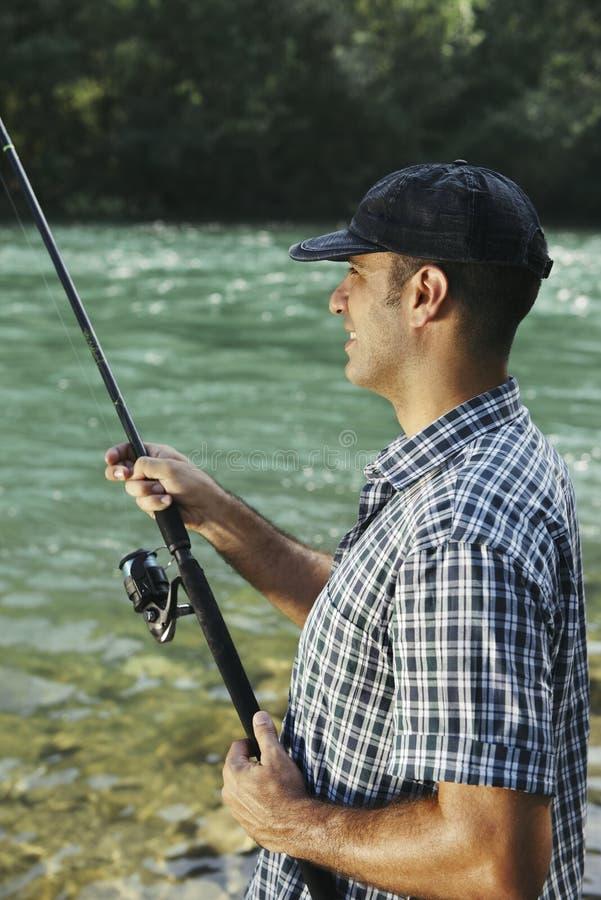 Rybak stoi blisko rzeki i trzyma połowu prącie fotografia royalty free