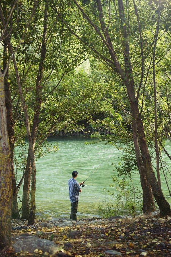 Rybak stoi blisko rzeki i trzyma połowu prącie zdjęcia stock