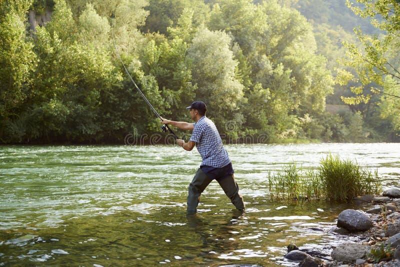 Rybak stoi blisko rzeki i trzyma połowu prącie zdjęcie stock