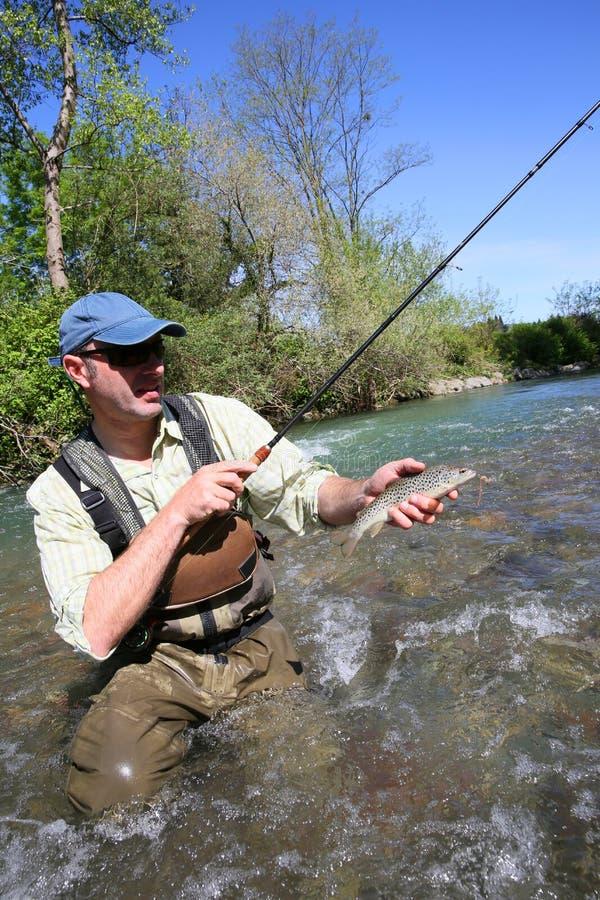 Download Rybak W Rzecznym Chwytającym Pstrąg Zdjęcie Stock - Obraz złożonej z woda, mężczyzna: 53780348
