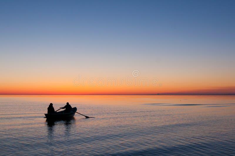 Rybak wioślarska łódź w se na wschodzie słońca zdjęcie stock