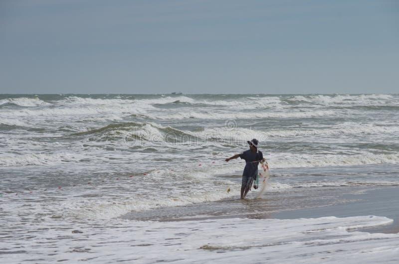 Rybak wyciąga wonton w wietrznym dniu na piaskowatej plaży w Mui Ne, Wietnam zdjęcia stock