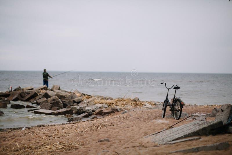 Rybak z rowerem na brzeg zatoka Finlandia w chmurnej pogodzie zdjęcia stock