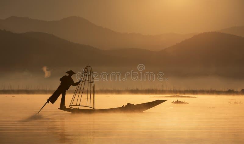Rybak z tradycyjną siecią na starej łodzi przy świtem obraz stock
