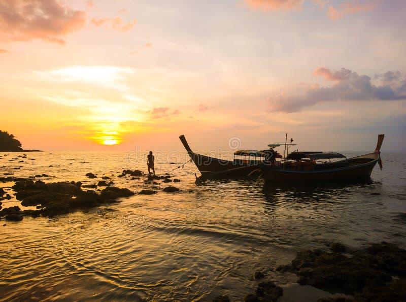 Rybak z zmierzchem i łodzią przy Koh Bulone wyspą, Satun Tajlandia zdjęcie stock