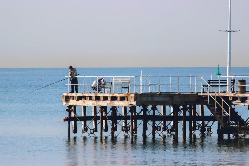 Rybaka połów z przędzalnianymi prąciami, rolki przy jezioro wodą zdjęcie stock