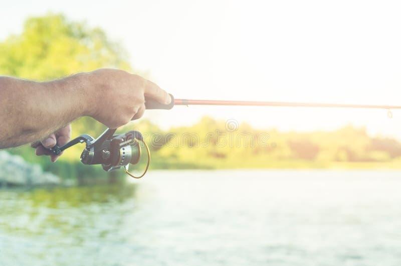 Rybaka ` s ręki z przędzalnictwem na tle woda zdjęcia stock