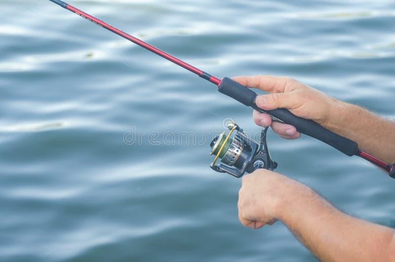 Rybaka ` s ręki z przędzalnictwem na tle woda fotografia royalty free