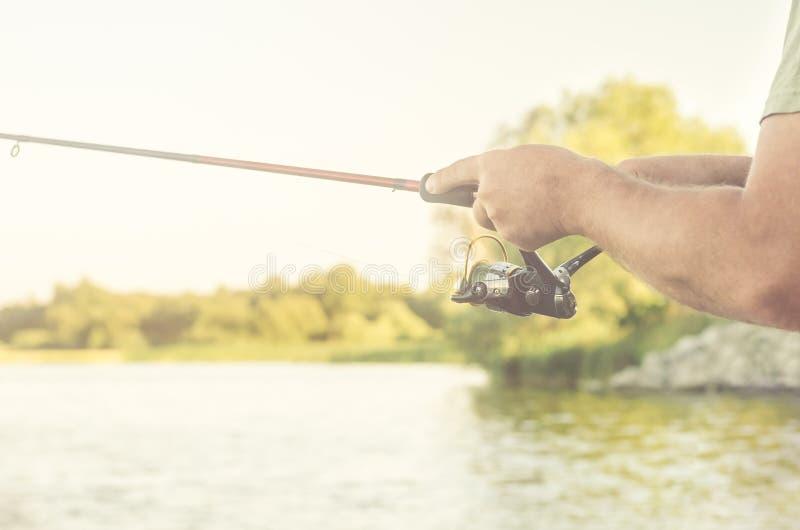 Rybaka ` s ręki z przędzalnictwem na tle woda zdjęcie royalty free