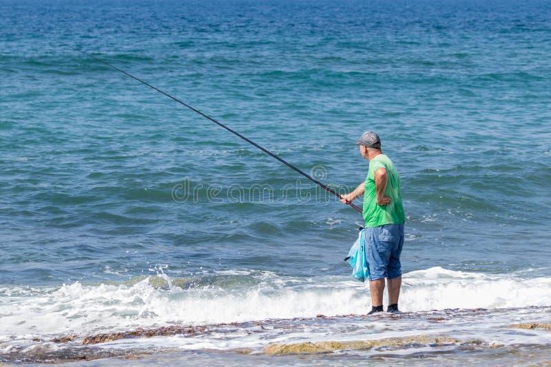 Rybaka stojaki w ryba z połowu prąciem na Śródziemnomorskim wybrzeżu blisko Nahariya miasta w Izrael i wodzie zdjęcie stock