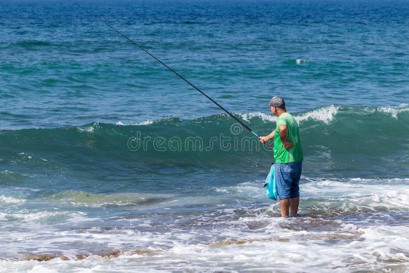 Rybaka stojaki w ryba z połowu prąciem na Śródziemnomorskim wybrzeżu blisko Nahariya miasta w Izrael i wodzie zdjęcia stock