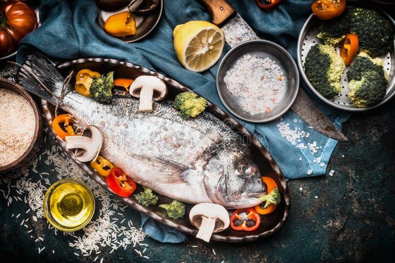 Rybi naczynia gotuje przygotowanie z dorado w wsparcie formie w kształcie ryba z zdrowymi warzywami na ciemnych nieociosanych tło zdjęcie stock